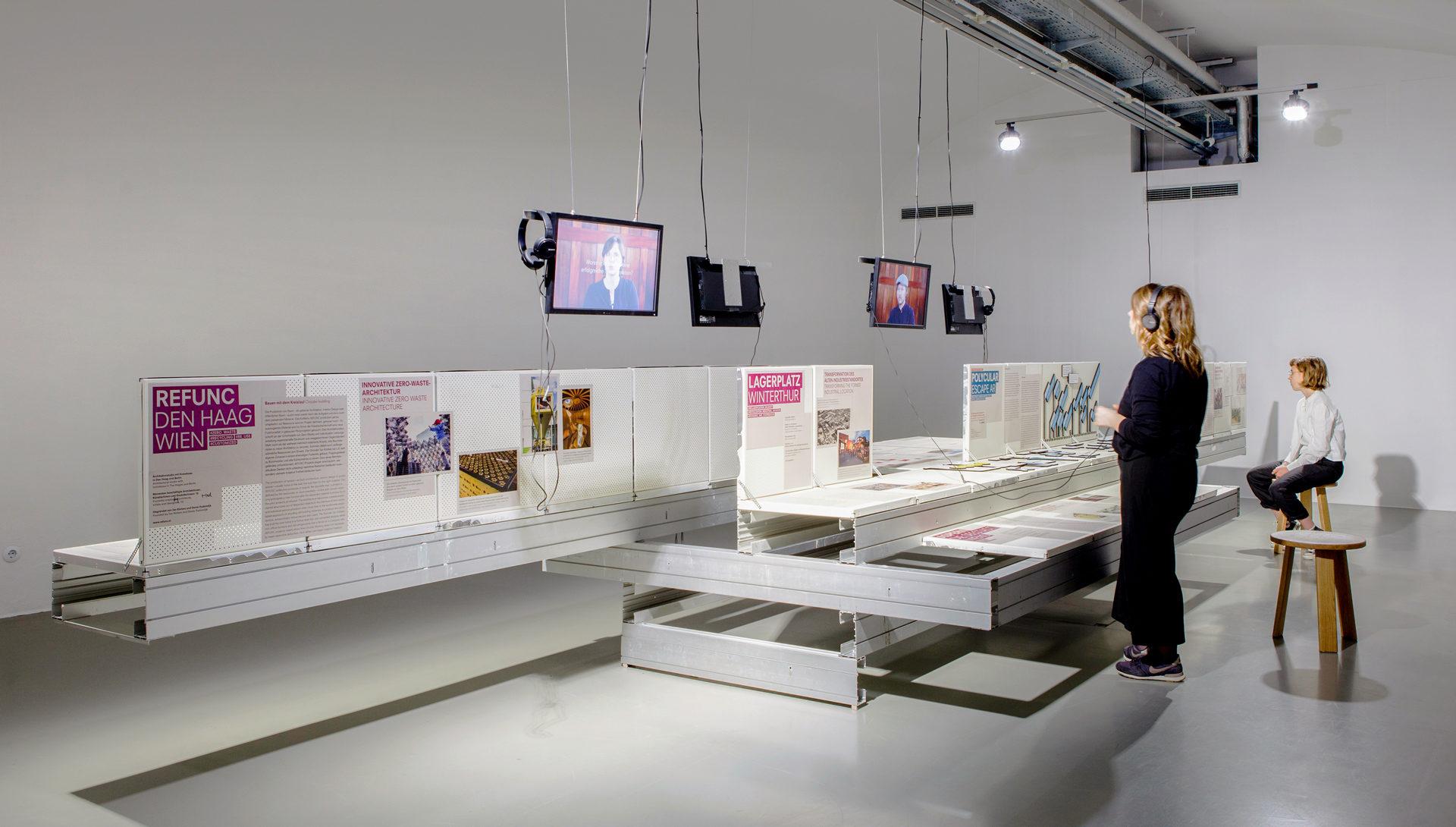 Detailansicht der Ausstellungsszenografie von Future Factory mit Display aus Metallkassetten, Fernsehern, Kopfhörern und Besucherinnen