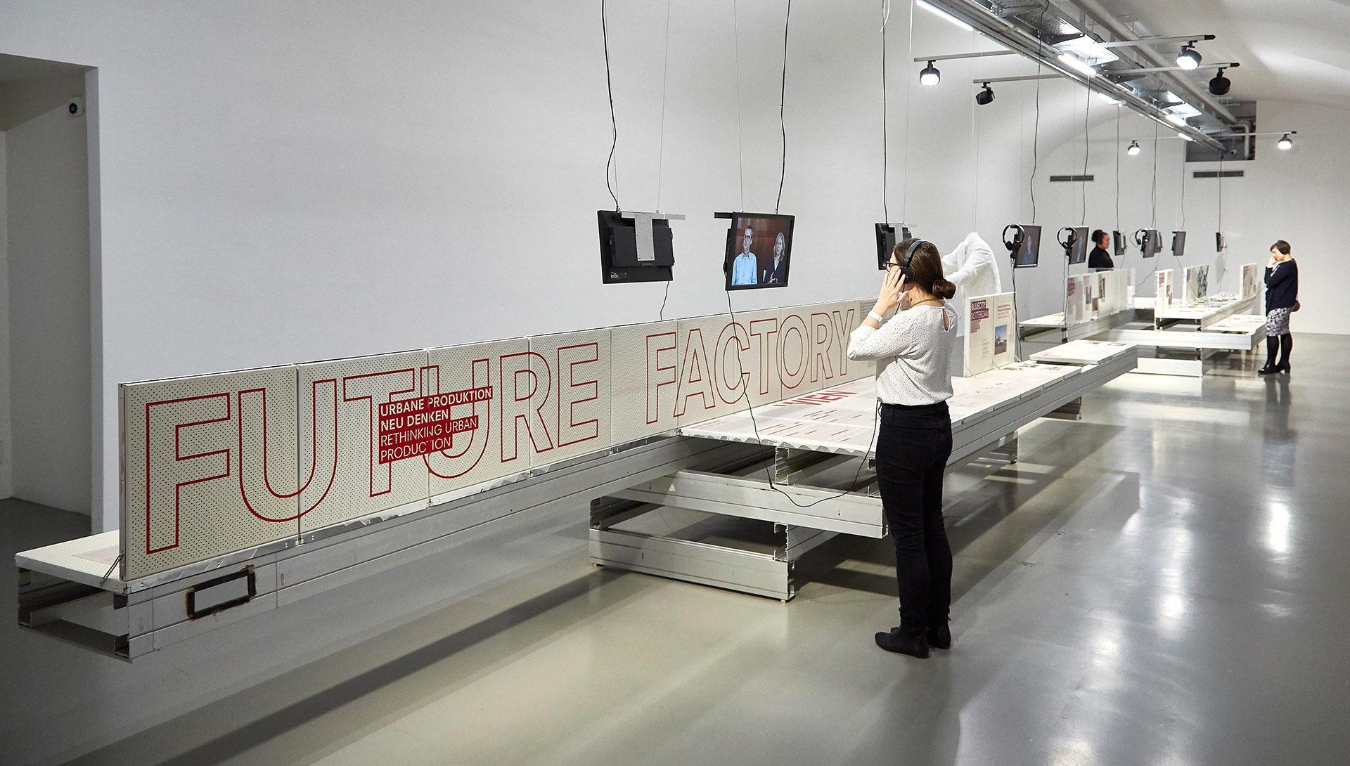 Ansicht des Ausstellungsraums der Future Factory mit Display für Projektbeispiele, Fernsehern für Interviews und Besucherinnen