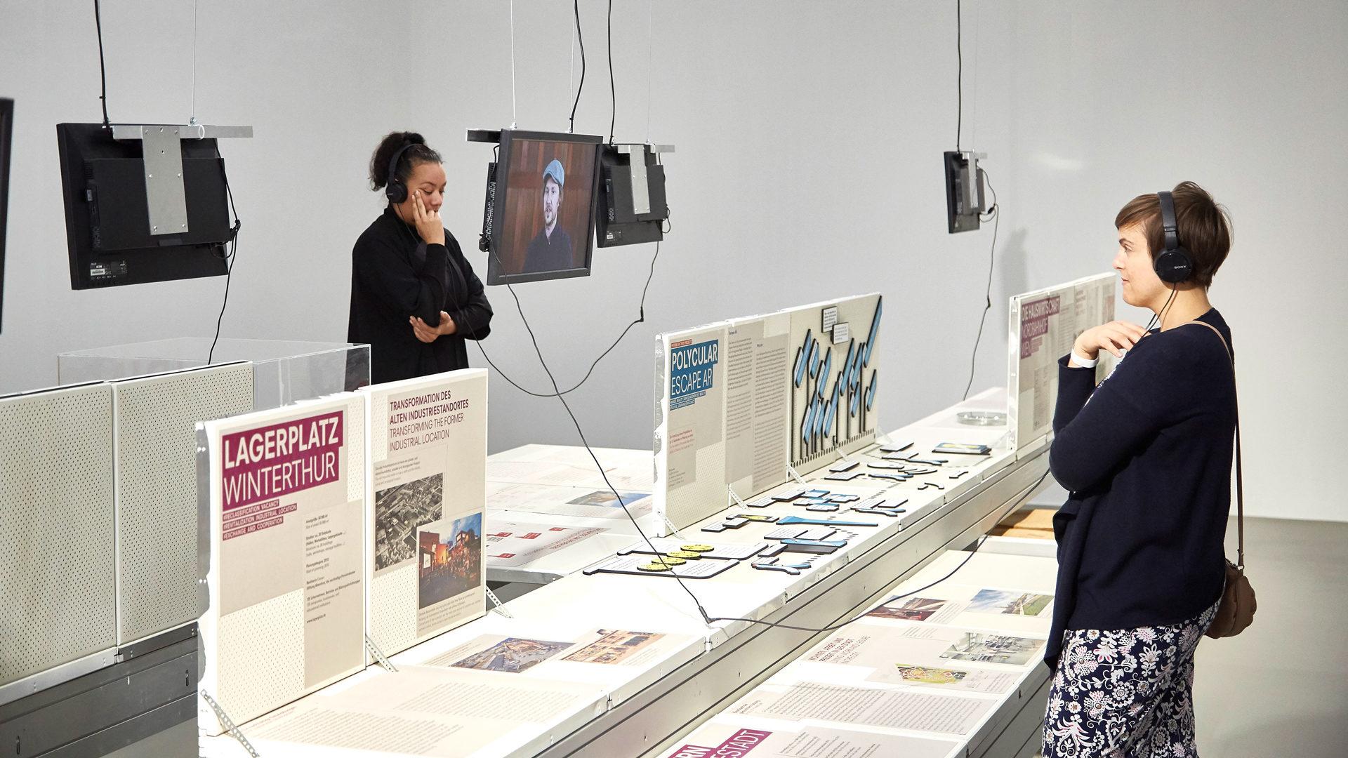 Ansicht aus der Ausstellung Future Factory mit Ausstellungsarchitektur, Fernsehern und 2 Frauen, die sich über Kopfhörer Interviews ansehen