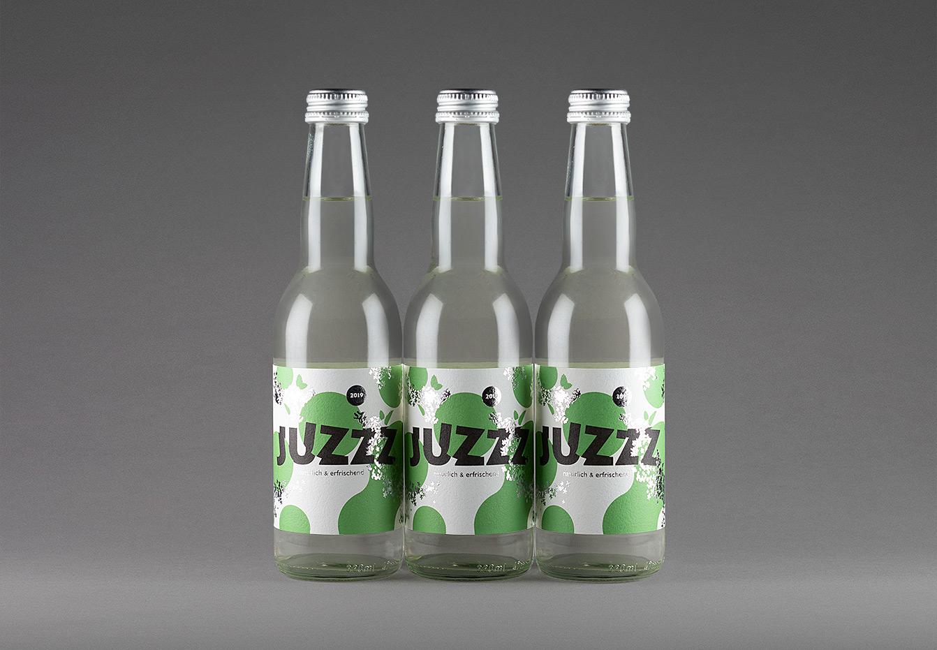 3 Flaschen des Erfrischungsgetränk Juzzz nebeneinander mit grün-silbernem Etikettedesign